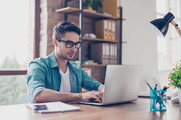 homem de calça jeans camisa e óculos sentado na mesa e typink uma carta para o seu conhecimento de espírito jovem bonito - college people laptop - fotografias e filmes do acervo