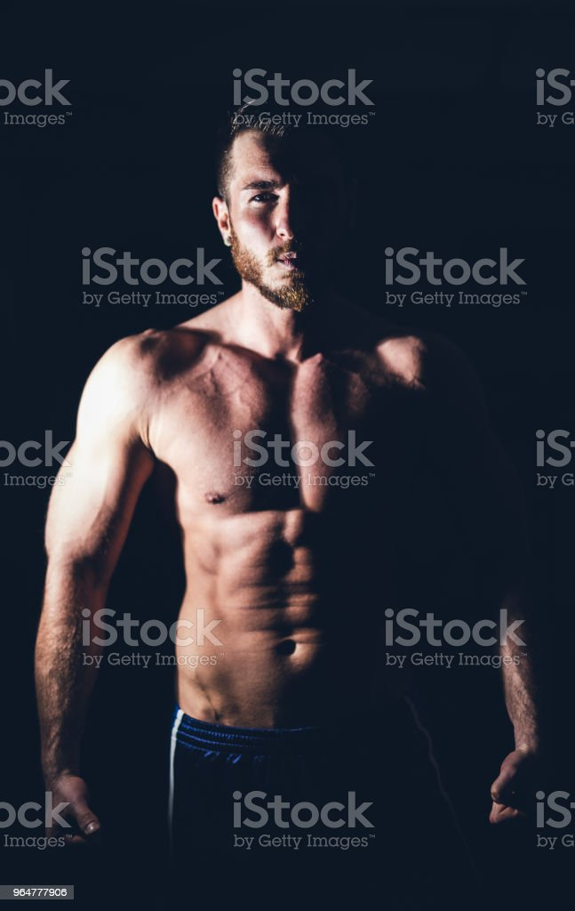 Young handsome muscular man in front of black background. royalty-free stock photo