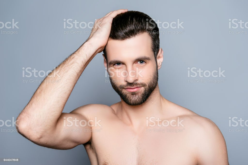 Young Handsome Naked Man Isolated On Gray Background Touching His Perfect Hair And Looking At Camera
