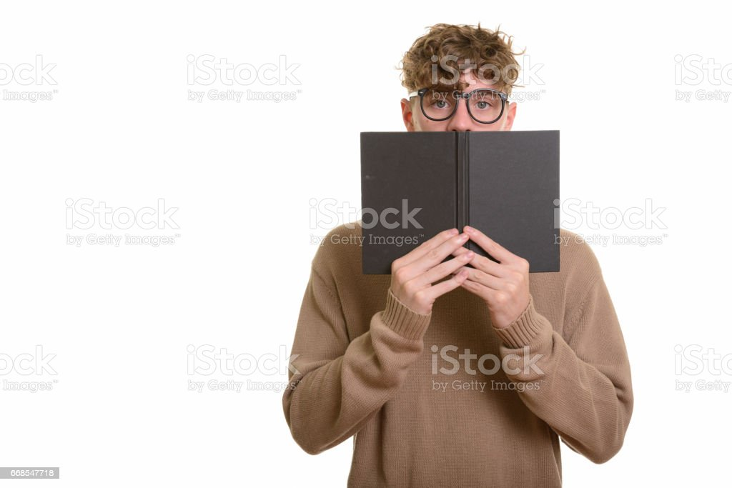 Young handsome nerd man wearing eyeglasses while hiding behind book stock photo