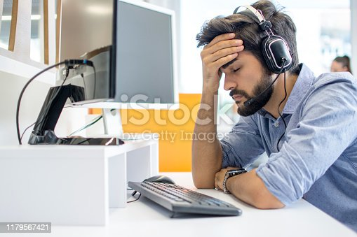 istock Young handsome operator man wearing call center headset suffering from headache 1179567421