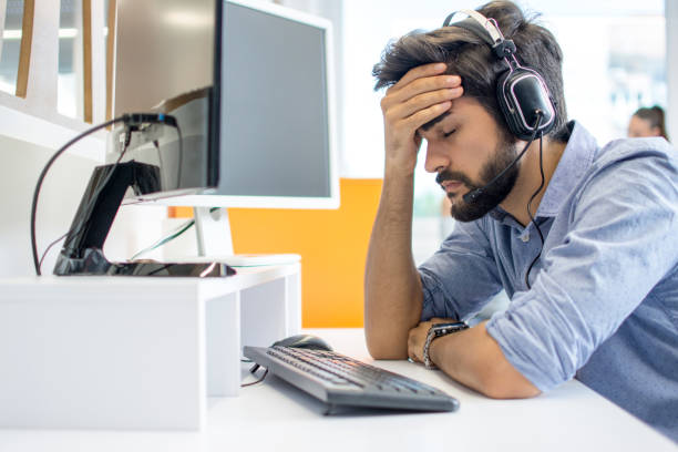 Young handsome operator man wearing call center headset suffering from headache stock photo