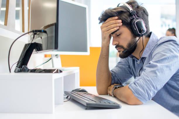 Junge stattliche Bediener Mann trägt Call-Center-Headset leiden unter Kopfschmerzen – Foto