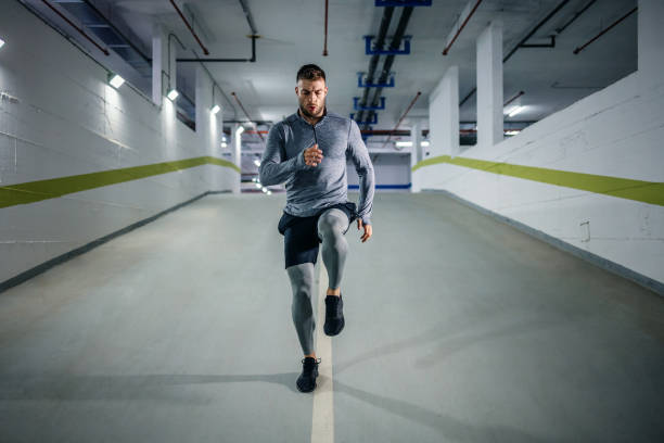 young handsome powerful muscular caucasian sportsman in active wear running in underground garage at night. urban life concept. - man city exercise abs foto e immagini stock