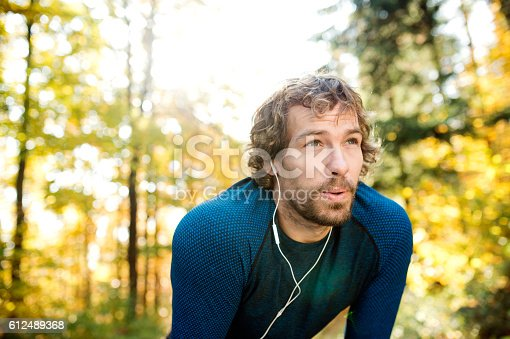 istock Young handsome runner with earphones outside in autumn nature 612489368