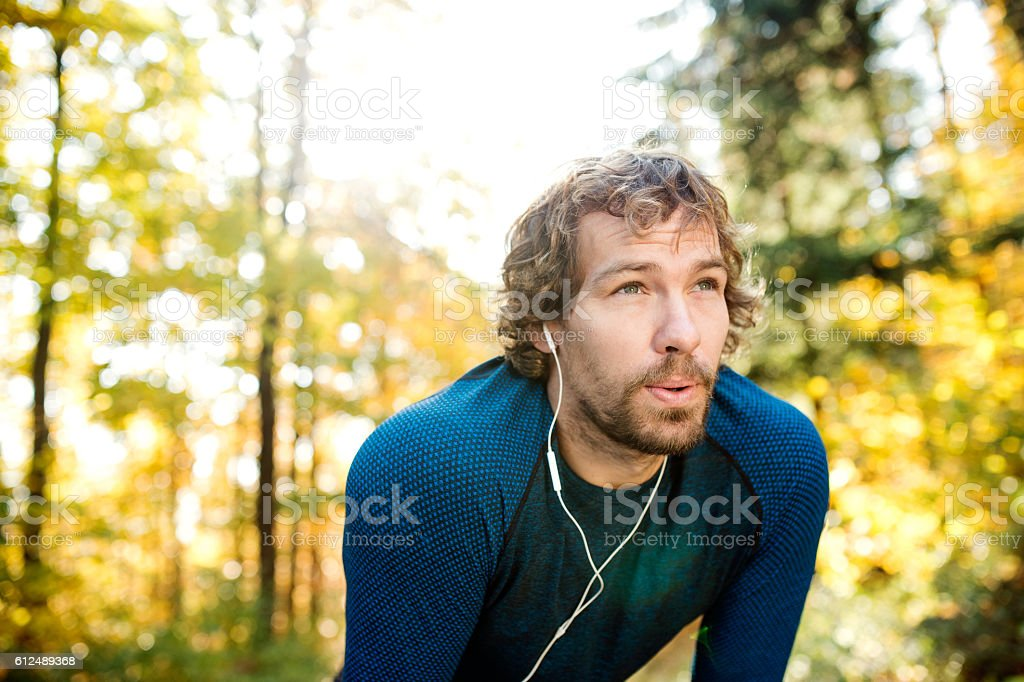 Young handsome runner with earphones outside in autumn nature stock photo