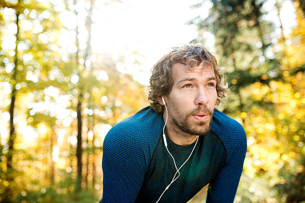 Young handsome runner with earphones outside in autumn nature - Photo