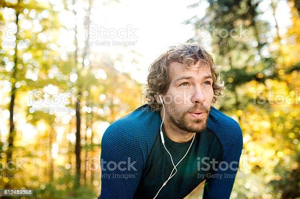 Junger Hübscher Läufer Mit Kopfhörern Draußen In Der Herbstnatur Stockfoto und mehr Bilder von Aktiver Lebensstil