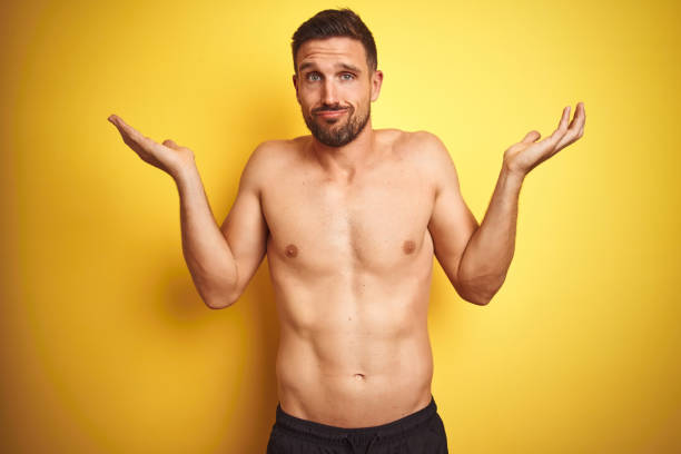 young handsome shirtless man over isolated yellow background clueless and confused expression with arms and hands raised. doubt concept. - a petto nudo foto e immagini stock