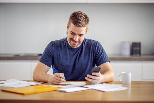 Young handsome smiling bearded man sitting at home, calculating budget and filling in bills. stock photo