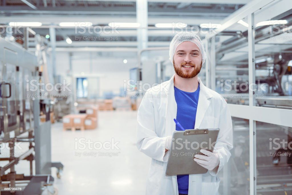 Young Handsome Smiling Scientist With Clipboard Posing in Factory stock photo