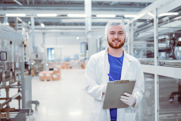 young handsome smiling scientist with clipboard posing in factory - quality control stock photos and pictures