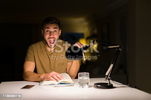 1175468850istockphoto Young handsome student man studying at night at home screaming proud and celebrating victory and success very excited, cheering emotion 1139065116