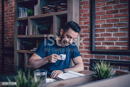istock Young Handsome Student Reading Book in a Modern Cafe Restaurant 929417338