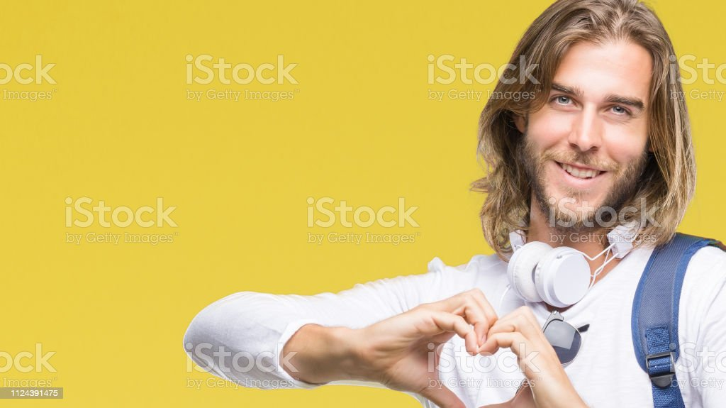 Young handsome tourist man with long hair wearing backpack over isolated background smiling in love showing heart symbol and shape with hands. Romantic concept. stock photo