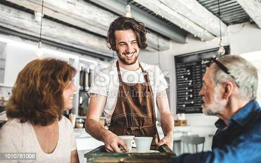 An attractive man with white t-shirt and brown apron serving older customers in a coffee shop.