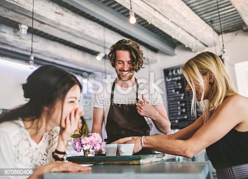 An attractive man with white t-shirt and brown apron serving female customers in a coffee shop.