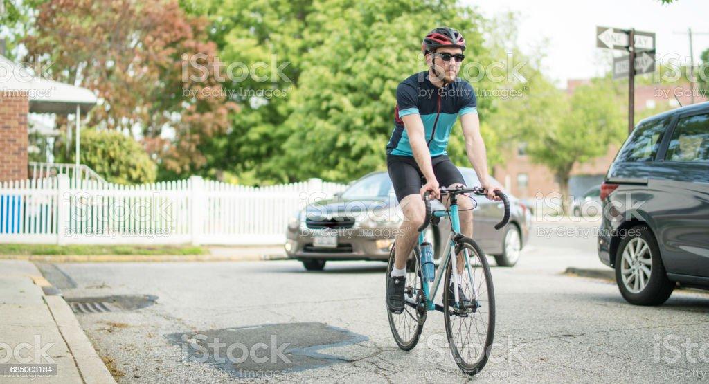 Schönen jungen gut ausgebildeten Mann tragen die Sportswear mit dem Fahrrad in die Wohnstraße in Queens, New York City Lizenzfreies stock-foto