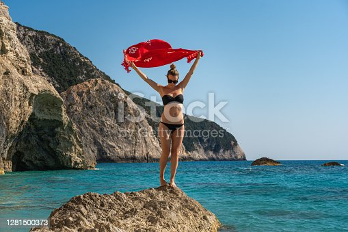 Young handsome woman holding her beach scarf in the wind on Porto Katsiki beach