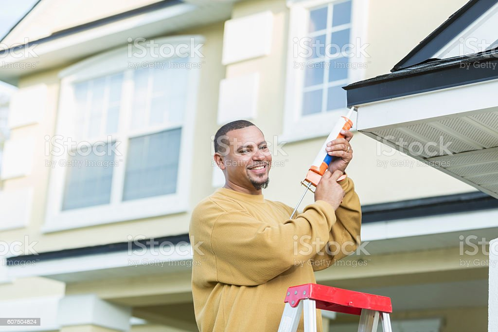 Young handyman doing house repairs stock photo