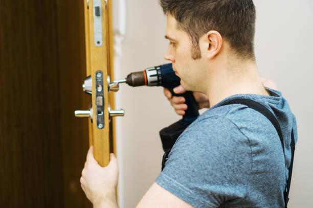 Young handyman in uniform changing door lock. stock photo
