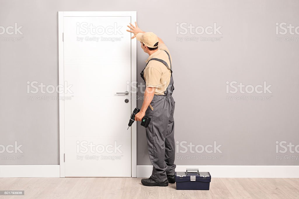 Young handyman installing a door stock photo