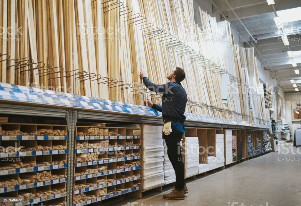 Young handyman selecting a length of cut timber stock photo