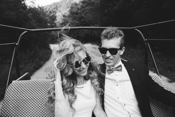 junge happe coupé in offenen wagen mit geschwindigkeit mit dem wind im haar. mode-stil, bw töne - rock n roll kleider stock-fotos und bilder