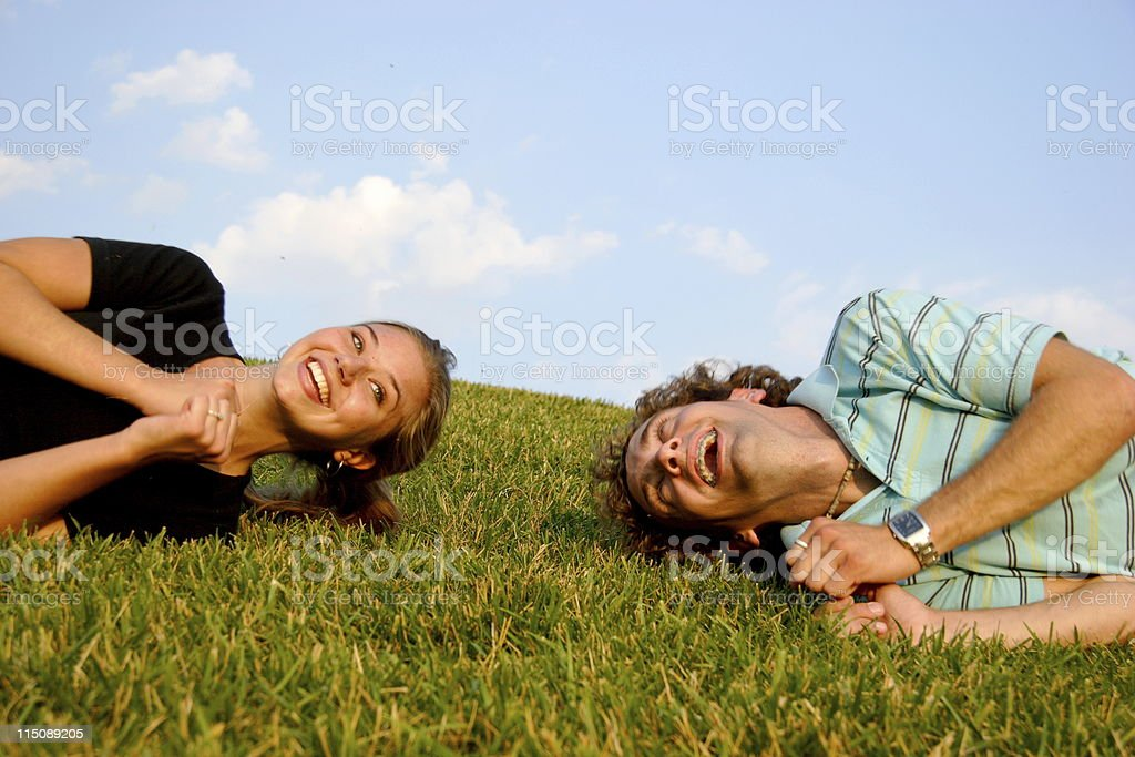 young happy adult couple playing on hillside royalty-free stock photo