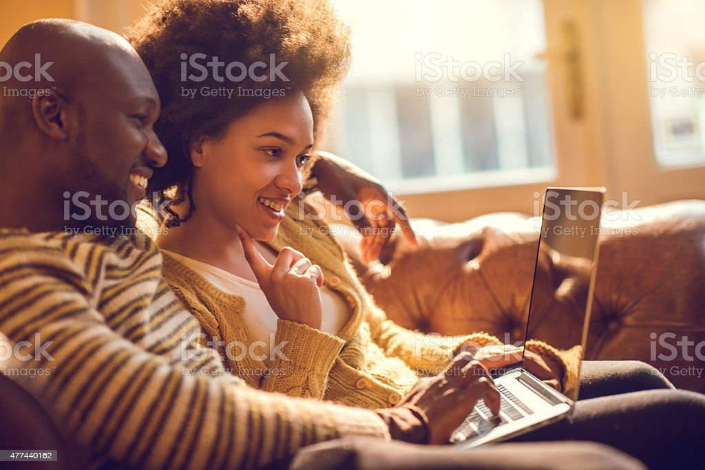 Young happy African American couple using laptop together. stock photo