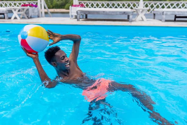 young happy african american man playing with ball in swimming pool - competition group stock photos and pictures