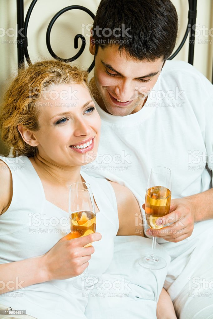Young happy amorous couple celebrating with champagne at bedroom royalty-free stock photo