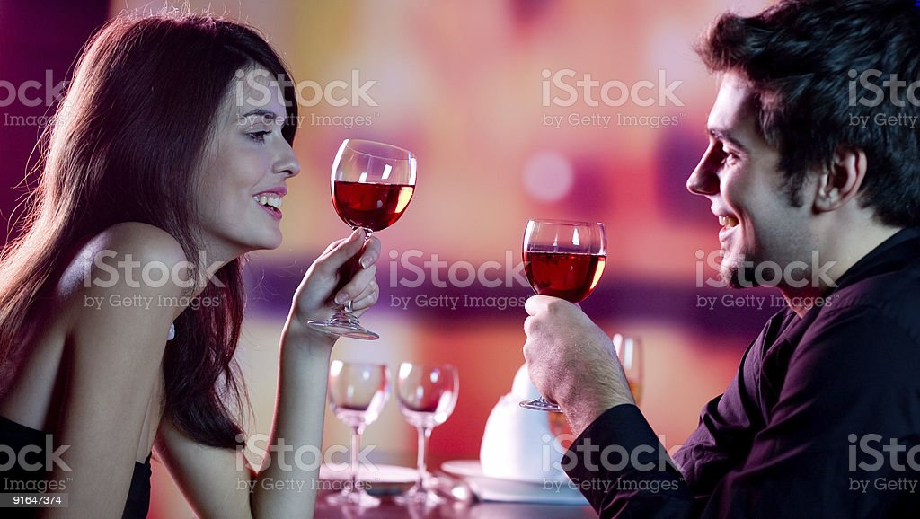 Young happy amorous couple celebrating with red wine at restaurant stock photo
