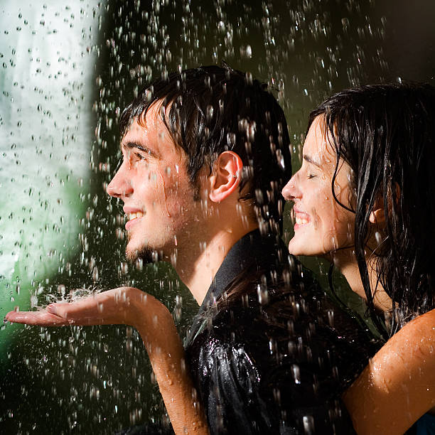 Young happy amorous couple hugging under a rain stock photo