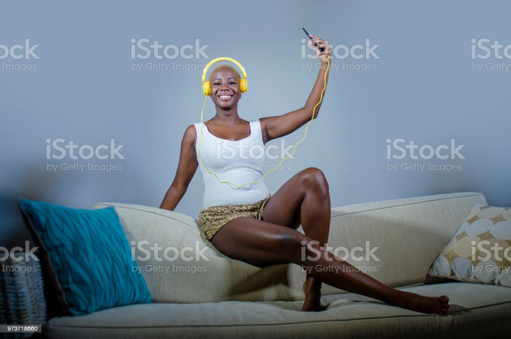 young happy and beautiful relaxed black afro American woman listening to music with headphones and mobile phone smiling cheerful enjoying song jumped at home sofa couch stock photo