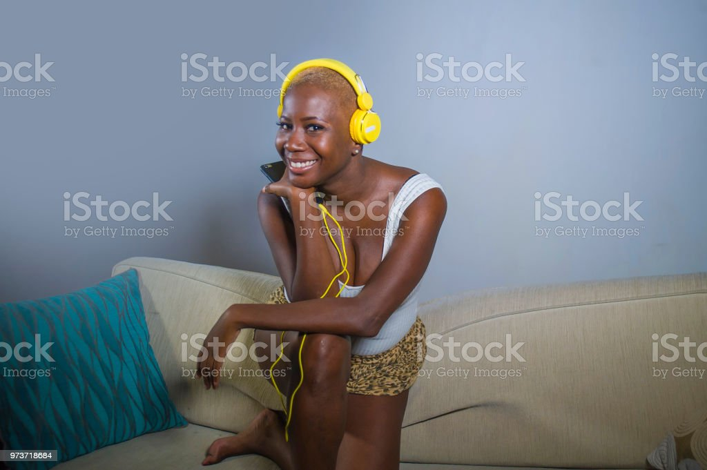 young happy and beautiful relaxed black afro American woman listening to music with headphones and mobile phone at home sofa couch smiling cheerful enjoying song lying comfortable and sweet stock photo