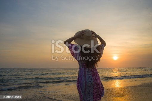 577645320 istock photo young happy and relaxed woman in Summer hat looking at the sun over the sea during an amazing beautiful sunset at tropical paradise beach in holidays travel and island tourism concept 1055440834
