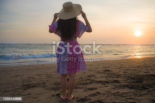 577645320 istock photo young happy and relaxed woman in Summer hat looking at the sun over the sea during an amazing beautiful sunset at tropical paradise beach in holidays travel and island tourism concept 1055440866
