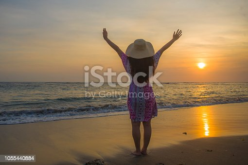 577645320 istock photo young happy and relaxed woman in Summer hat looking at the sun over the sea during an amazing beautiful sunset at tropical paradise beach in holidays travel and island tourism concept 1055440884