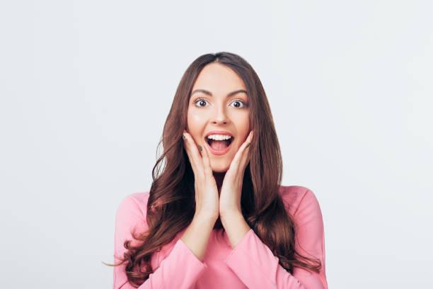 Joven mujer feliz y sorprendido mirando a la cámara y sostiene las mejillas con las manos aisladas en la espalda blanca - foto de stock