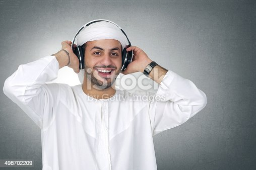 istock Young happy Arabian man with headphones listening to music 498702209