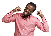 istock Young happy arfican man smiling, listening music via earphones, dancing with closed eyes isolated on white background 1246968546