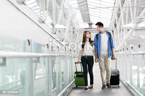 842907838 istock photo Young happy asian couple carrying suitcase luggage in airport terminal. Couple holding hand and traveling abroad together, Air travel or holiday vacation concept 857353600