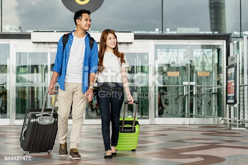 842907838 istock photo Young happy asian couple carrying suitcase luggage in airport terminal. Couple holding hand and traveling abroad together, Air travel or holiday vacation concept 944431472