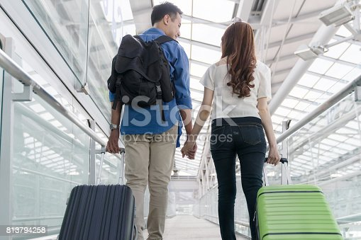 842907838 istock photo Young happy asian couple form back view  carrying suitcase luggage in airport terminal. Couple holding hand and traveling abroad together, Air travel or holiday vacation concept 813794258