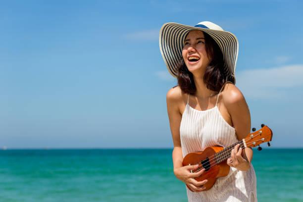 junge asiatische frau glücklich ukulele spielen und singen auf den strand und blauer himmel im hintergrund, sommer und urlaub konzept, textfreiraum - ukulele songs stock-fotos und bilder