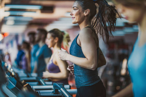Young happy athletic woman jogging on treadmill during sports training in a gym. stock photo