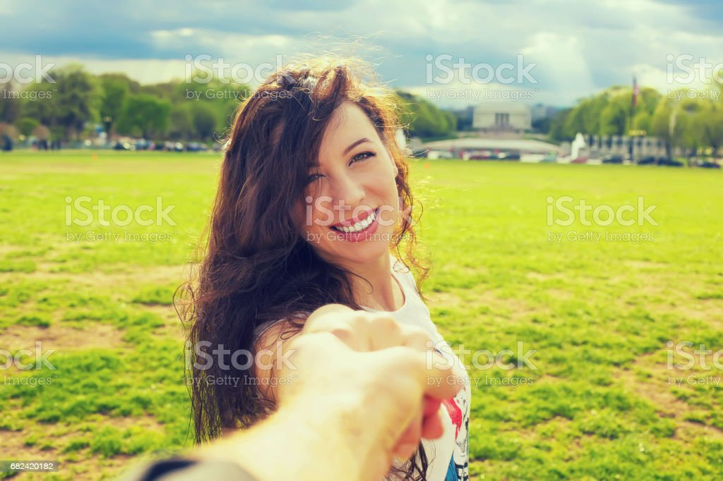 Young happy beautiful woman leading man royalty-free stock photo
