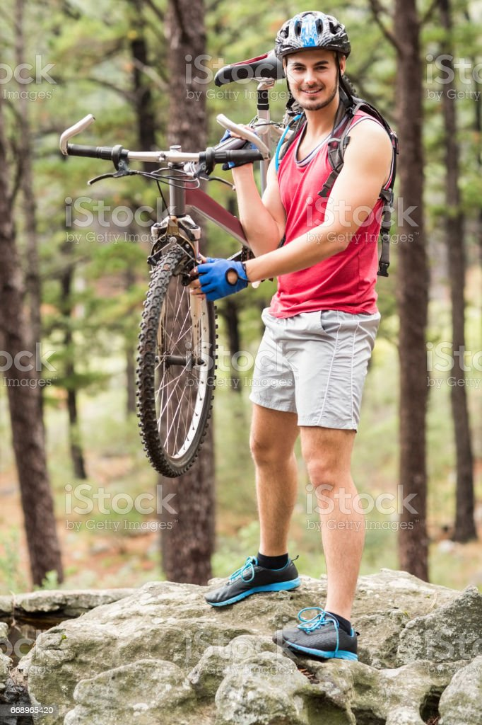 Young happy biker holding bike on a rock foto stock royalty-free