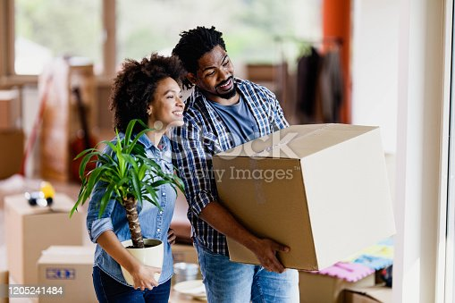 Happy African American couple moving into new apartment and looking through window. Focus is on man.